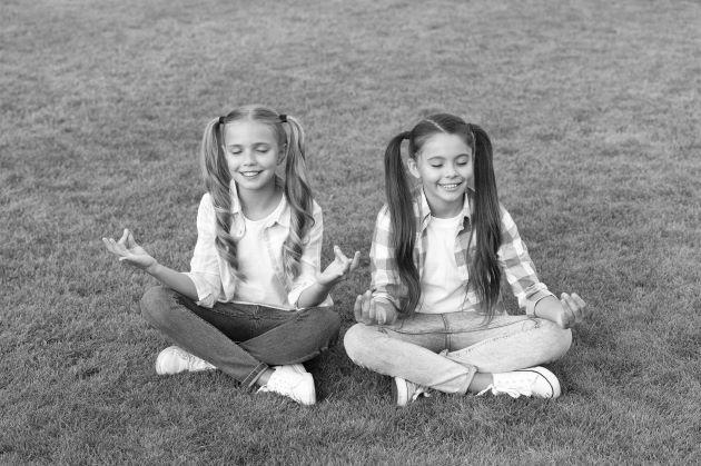 Enfants apprenant à méditer dans un parc, photo noir et blanc.