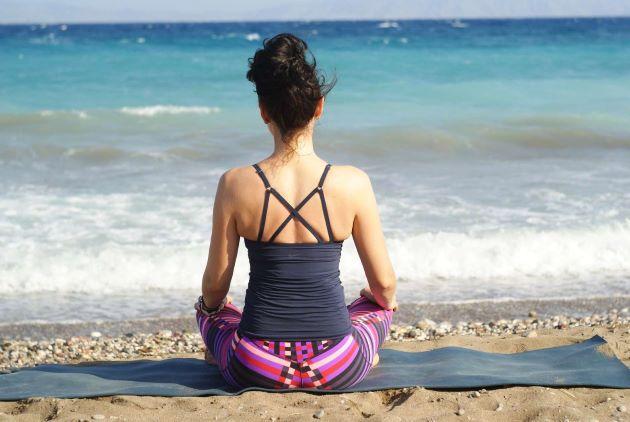 Femme de dos méditant sur la plage au calme