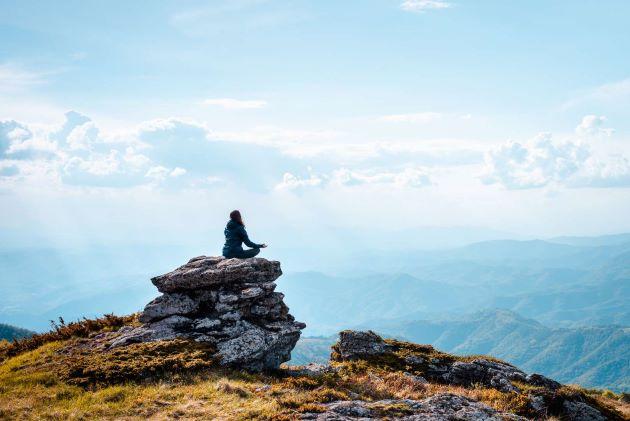 Femme méditant sur un rocher en haut d'une montagne