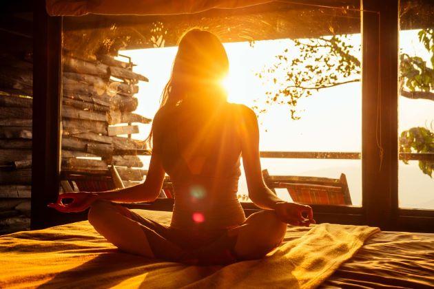 Femme en position du lotus, méditant au levé du soleil