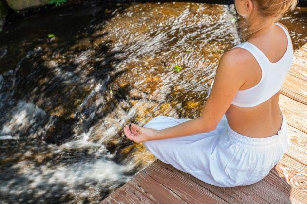 Femme en position birmane médite au bord d'une rivière en tenue confortable