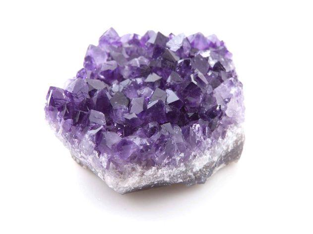 Amas d'améthyste violet foncé sur fond blanc.