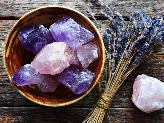 Bol en bois contenant des cristaux d'améthyste brutes posés à côté d'un bouquet de lavande et d'un cristal de quartz rose.
