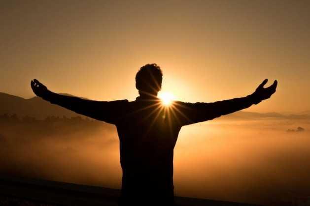 Les bienfaits de la méditation. Un homme ouvrant les bras au lever du soleil sur la montagne.