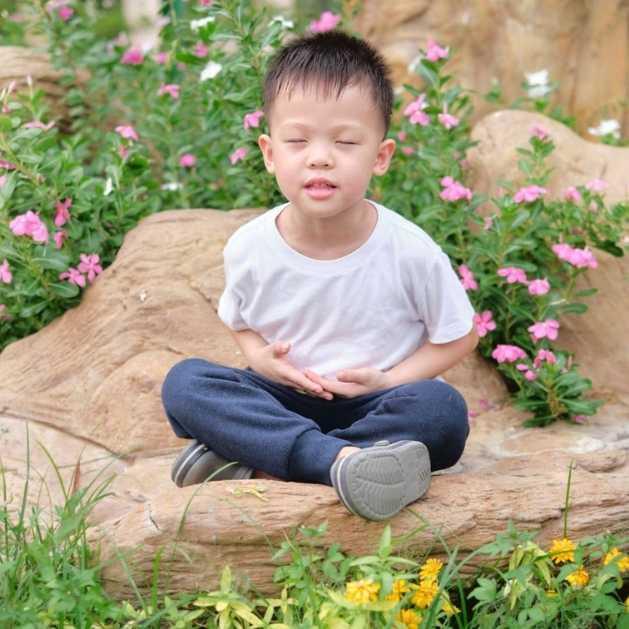 Pourquoi méditer ? Enfant heureux méditant dans un jardin fleuri.