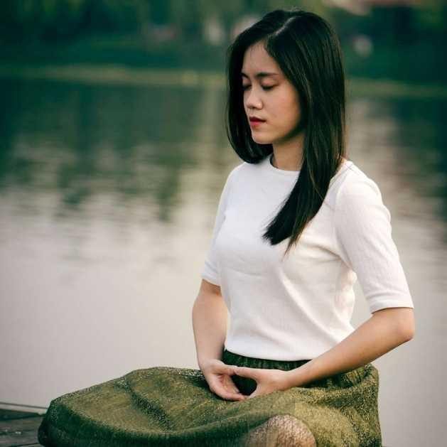 Femme qui médite au bord d'un lac en lotus. Premiers pas en méditation