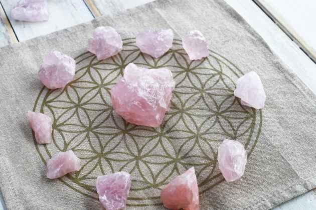Plusieurs quartz roses déposés sur une fleur de vie pour une purification.