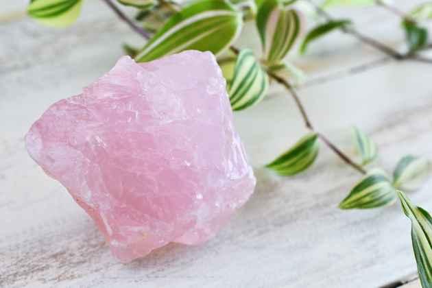 Photo lumineuse d'un quartz rose brut sur fond en bois avec une plante verte.