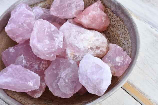 Bol en terre cuite contenant des pierres brutes de quartz rose.