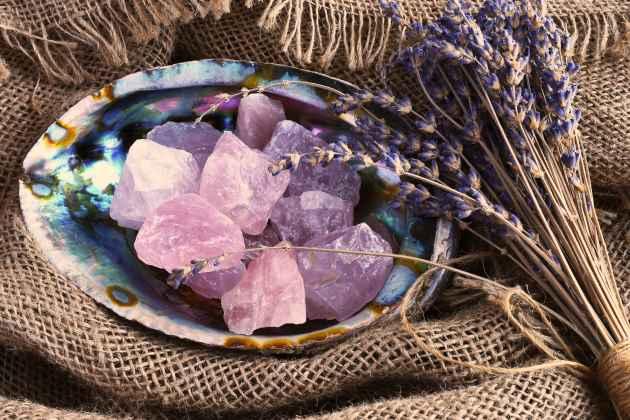 Coquille d'ormeaux contenant des cristaux de quartz rose avaec un bouquet de fleurs de lavande.