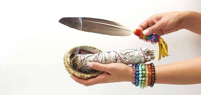 coquille d'ormeau avec une sauge blanche et une plume sauvage sur une bras et des minéraux en pierres naturelles